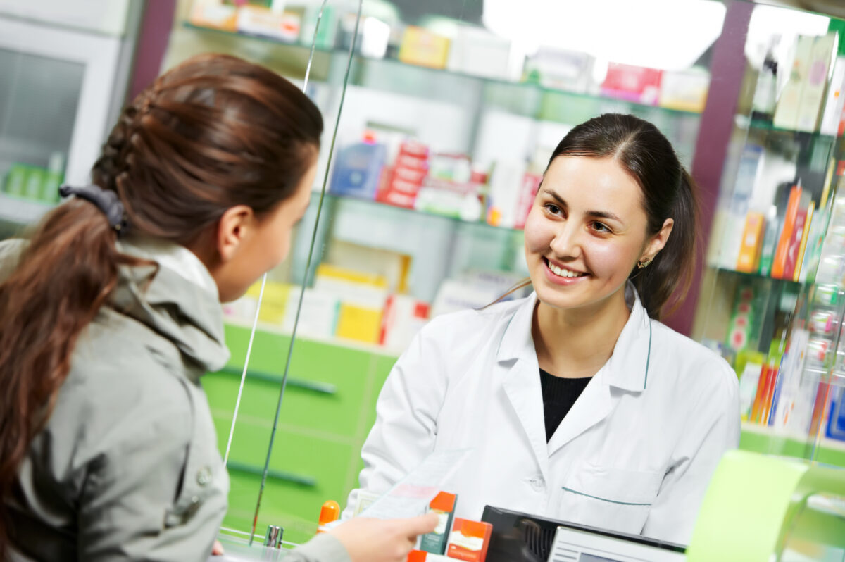 Image of a customer speaking to a pharmacy assistant