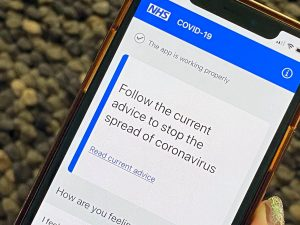 A mobile phone displaying the NHS Track and Trace web page.