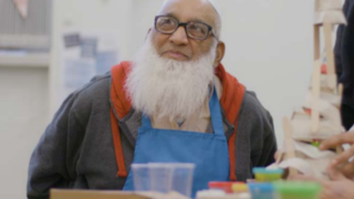 A portrait of a South Asian older male looking happy